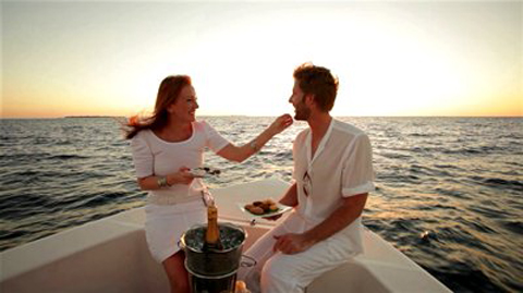 stock-footage-young-couple-in-white-sitting-on-boat-at-sunset-with-champagne-and-appetizer